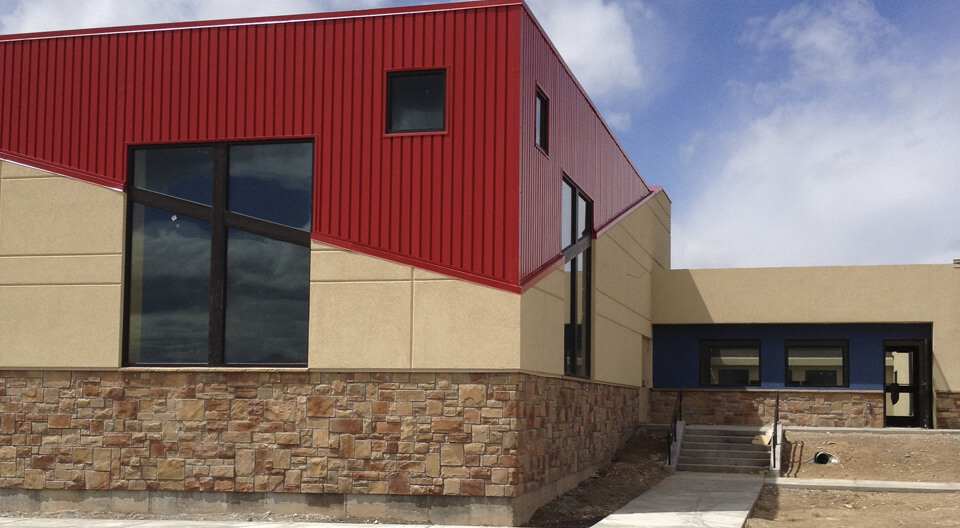 Washington Heights Addition in Ogden, UT - stucco siding with score lines - metal red siding-stone masonry work - Kids zone churches - tall windows - diagonal lines in buildings