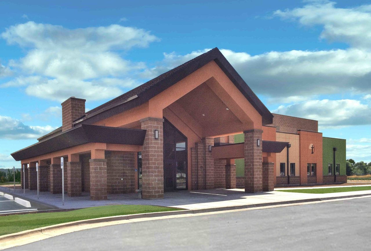 Idaho worship and community center. Church architecture church design. Mountain West Architects. Brick church exterior. Storefront church entrance. Gabled roof overhang church entrance.