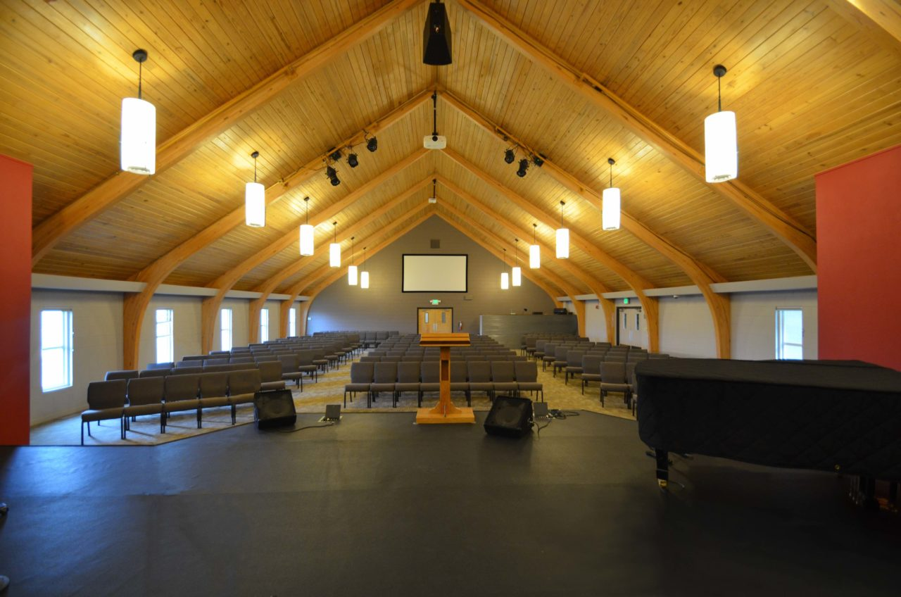 Calvary Community Baptist Church renovation Colorado. Mountain West Architects. Simple church design, simple church layout, minimalistic church layout, pendant lighting, exposed wood rafters in churches, wood ceiling in church. Spacious church stage. Large church screen. warm church color scheme