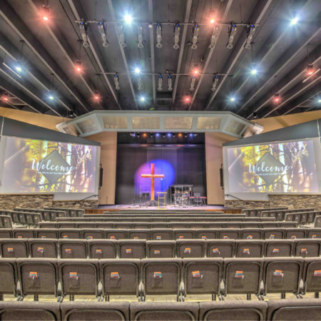 Picture of Pulpit Rock Auditorium Renovation, pendant lights, large worship seating, balcony viewing area in churches, glass partition in church assembly, exposed rafters in church interior, modern church sanctuary, wood trim in interior church building. Bright church auditorium. Large TV in church auditorium. Center stage church auditorium.