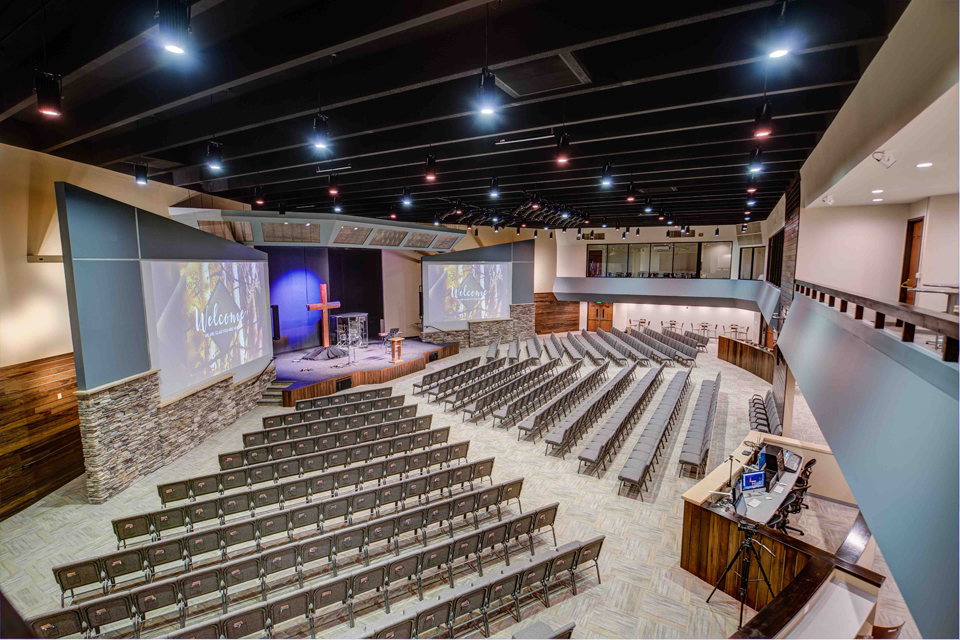 Picture of Pulpit Rock Auditorium Renovation, pendant lights, large worship seating, balcony viewing area in churches, glass partition in church assembly, exposed rafters in church interior, modern church sanctuary, wood trim in interior church building, modern church auditorium, multiple level church auditorium, church mezzanine