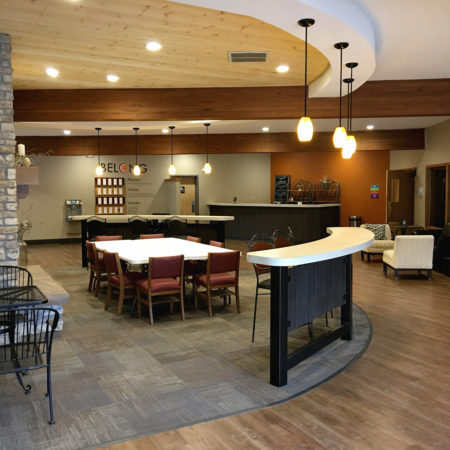 Pendant lightning, church foyer and lobby area, exposed wood framing, church café, warm church cafe color scheme, stone column, wood floor finish, wood ceiling