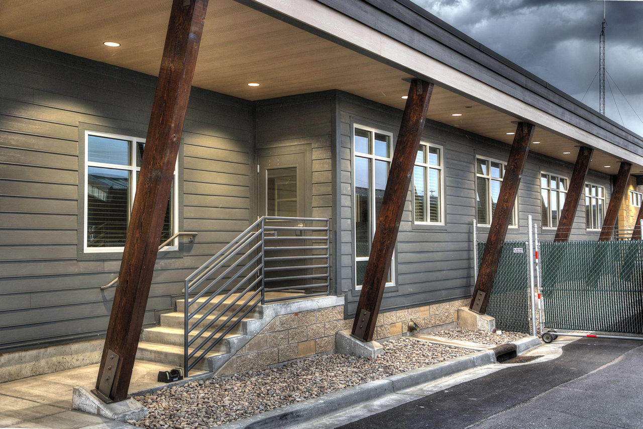 Wood siding, canned lights, exposed wood columns, exposed wood supports, neutral exterior color scheme